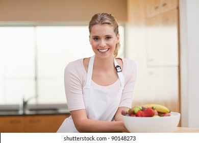 Woman posing with a fruit basket in her kitchen