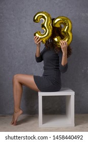 Woman posing with gold foil balloons, 33 years old celebration. Happy birthday!