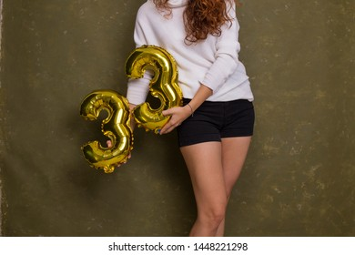 Woman posing with gold foil birthday balloons, thirty three years old birthday party. Unrecognizable woman holding number 33
