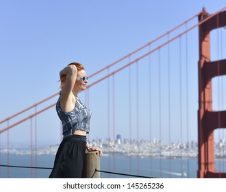 Woman posing with golden gate bridge and San Francisco city background.