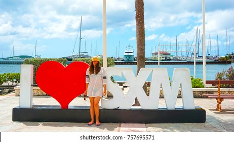 The woman posing near sign and statue I love St Martin in Marigot, St .Maarten island