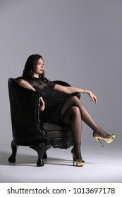 Woman posing on the armchair. Gray background. Photographie retouchee