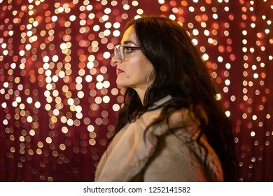 Woman posing for photo in front of light wall at Christmas market.