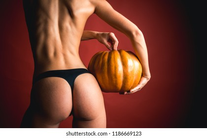 Woman posing with Pumpkin. Buttocks ass and pumpkin close-up. Huge buttocks. Great ass and pumpkin. Pumpkin - funny concept. Trick or treat