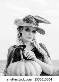 Woman posing with Pumpkin. Halloween Witch with in magic hat. Beautiful young surprised woman in witches hat and costume holding pumpkin. Attractive model girl in Halloween costume