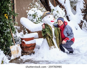 Woman is posing with a snowman in her front yard during snow storm