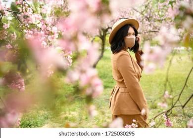 Frauen posieren mit einer Gesichtsmaske, die mit Blumen geschmückt ist. Stilvolle handgefertigte Baumwollmaske. Frühlingsblütengarten