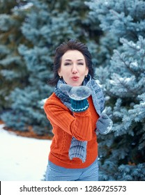 Woman is posing in winter forest, beautiful landscape with snowy fir trees. Dressed in red sweater. Blowing a kiss.