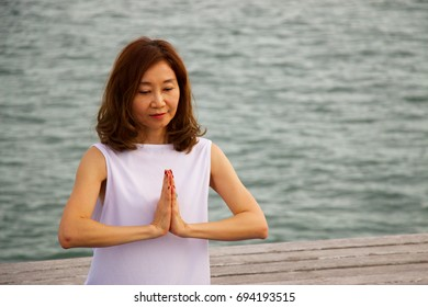 Woman is posing yoga meditation at pier