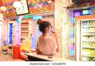 Woman posting in front of Colorful Japanese vending machines