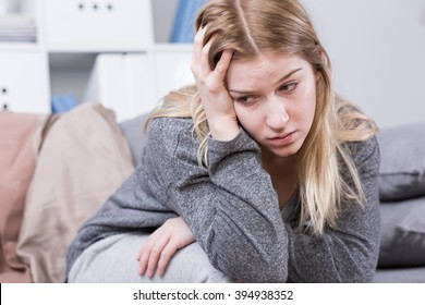 Woman with postpartum depression, sitting exhausted on sofa, holding hand on her head