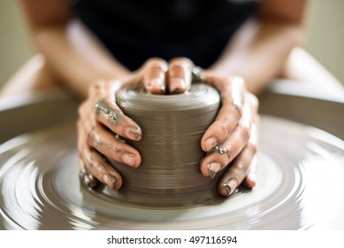 woman potter hands makes on the pottery wheel clay pot