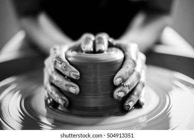 woman potter hands makes on the pottery wheel clay pot , black and white