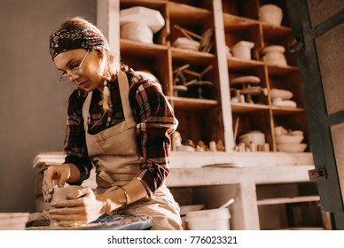 Woman potter making a clay pot on pottery wheel in workshop. Craftswoman moulding clay with her hands on pottery wheel.