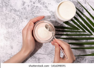 女性は、モーニングスムージーやヨーグルトにコラーゲン粉末やタンパク質を注ぐ。自然の美しさと健康の補足。健康的なライフスタイル。平面図、上面図。スペースをコピーします。