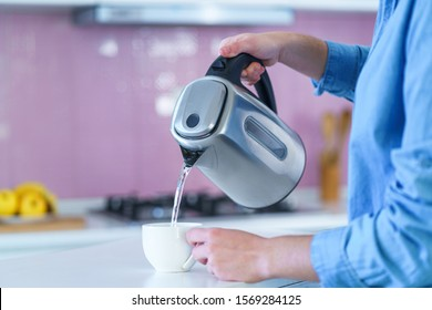 Woman pouring boiled water in a cup from an electric kettle for brewing hot tea at home at kitchen