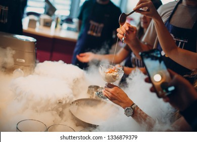 Woman pouring caramel syrup over  ice cream made with liquid nitrogen.