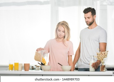 woman pouring cereal in bowl during breakfast near man at kitchen
