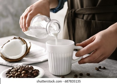 Woman pouring coconut milk into cup of coffee on table