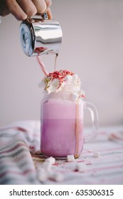 Woman is pouring coffee in stylized mason jar cup of colored milk with cream, marshmallow and colorful decoration. Milk shake, cocktaill, frappuccino.  Unicorn coffee, unicorn food.
