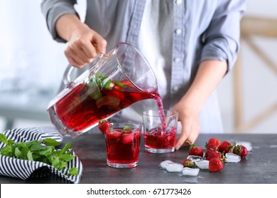 Woman pouring delicious strawberry lemonade into glass