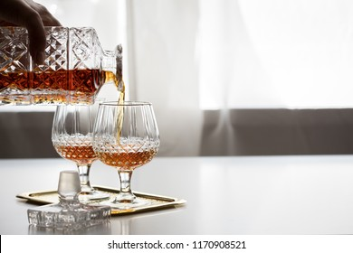 Woman pouring and drinking brandy of lead crystal bottle in cognac snifter glasses