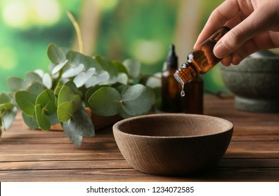 Woman pouring eucalyptus essential oil into bowl on wooden table