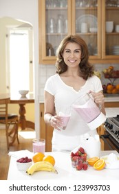 Woman pouring a fruit smoothie looking at camera, in kitchen setting with fruit on counter