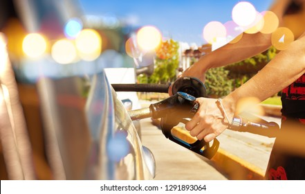 Woman pouring gasoline into the car at the service station.fuel station and car concept