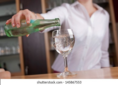 Woman pouring a glass of mineral water into a wineglass from a glass bottle