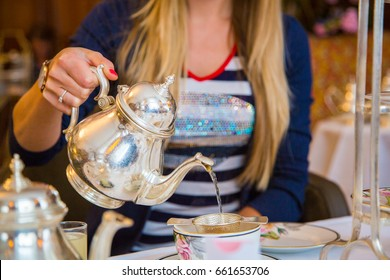 Woman pouring green tea in mug from teapot at the afternoon tea ceremony