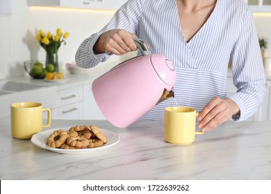 Woman pouring hot water from modern electric kettle in cup indoors, closeup
