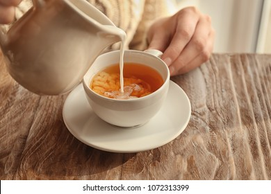 Woman pouring milk into cup with aromatic tea on table