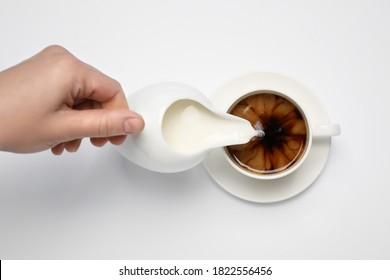 Woman pouring milk into cup of coffee on white background, top view