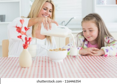 Woman pouring milk into a glass for daughter and smiling