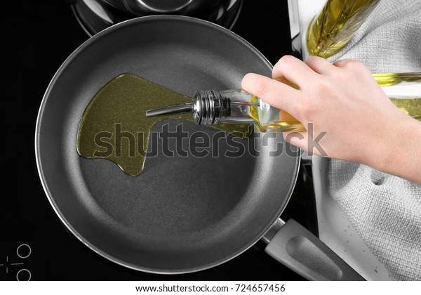 Woman pouring oil from bottle into frying pan in kitchen