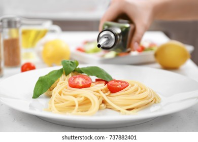 Woman pouring pasta with olive oil on plate
