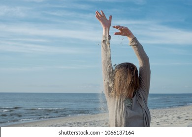 Woman pouring sand on her head on the beach
