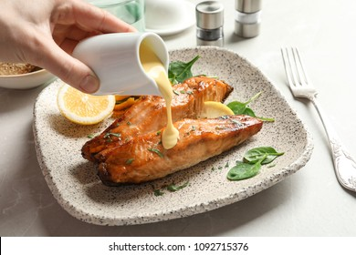 Woman pouring sauce onto tasty cooked salmon on plate, closeup