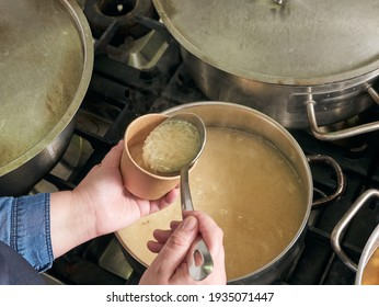 woman pouring soup on takeaway containers, no faces shown