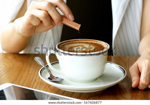 Woman pouring sugar in coffee cup, Sugar addicted consuming concept.