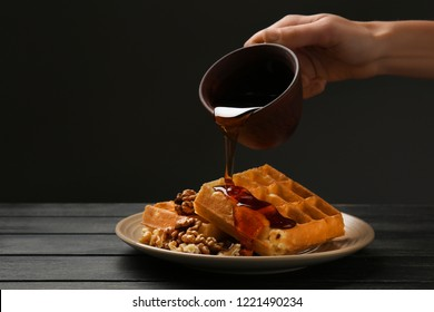 Woman pouring syrup on tasty waffles against dark background