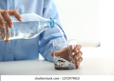 Woman pouring water into glass on table
