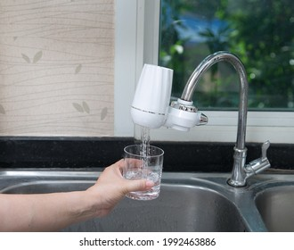 woman pouring water into glass from the water filter in the kitchen. Pouring clean fresh drink.
