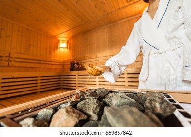 Woman is pouring water into hot stone in Sauna spa room