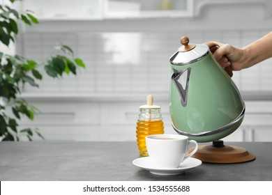 Woman pouring water from modern electric kettle into cup at grey table in kitchen, closeup. Space for text