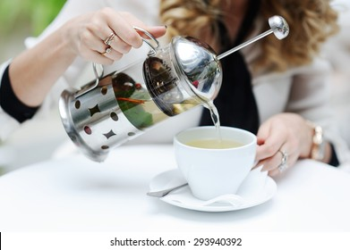 woman pours green tea from teapot into a cup