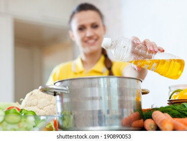 Woman pours oil from bottle into the pan. Focus on bottle