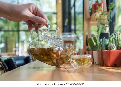 Woman pours tea flowers from a teapot