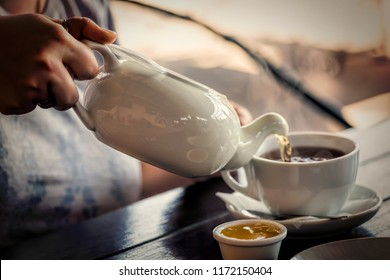 woman pours tea into a cup. Closeup, breakfast, tea-party